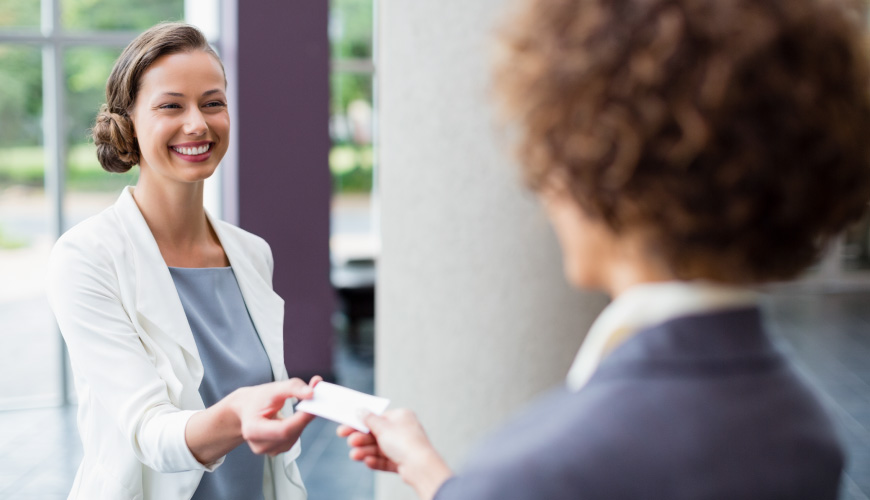 Women handing out business cards